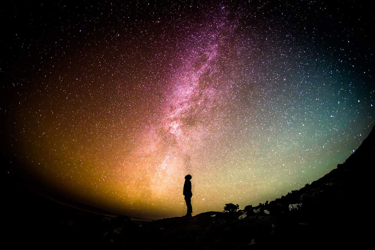 Astrophoto of man standing in front of Milky Way